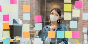 woman-brainstorming-at-the-office-while-wearing-a-facemask-picture-id1287294863 (1)